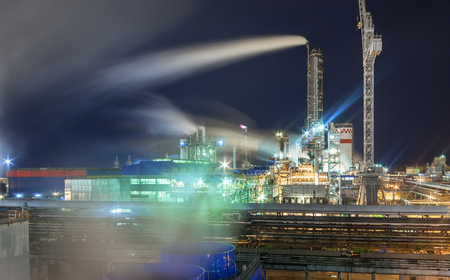 amoniaco: Steam from the cooling tower against the background of a pipeline and a chemical plant at night