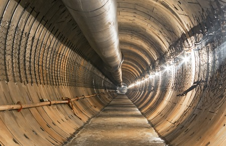 Empty tunnel under construction for the metro. Large temporary ventilation pipe under the ceiling subway tunnel. Focus on the center of the frame