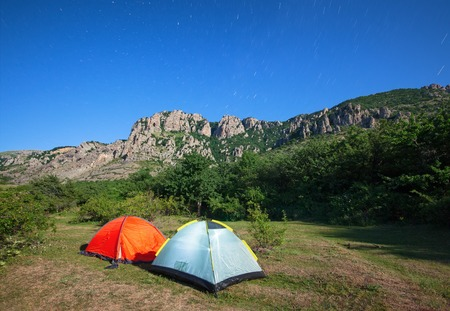 Tourist tents in a clearing in the mountains against the starry sky and the mountain peak