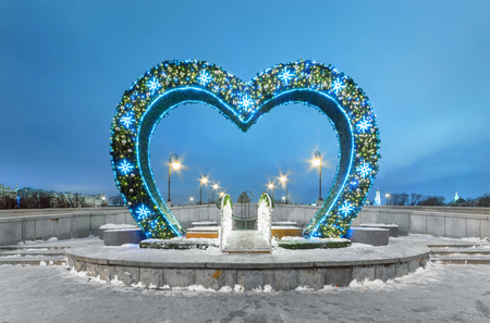 Arch of lovers in the shape of a heart decorated for Christmas and New Year on the bridge at night