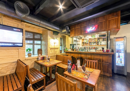 MOSCOW - AUGUST 2014: The interior of the beer bar SHTIRBEERLITZ. Bar hall with wooden furniture and wooden bar counter