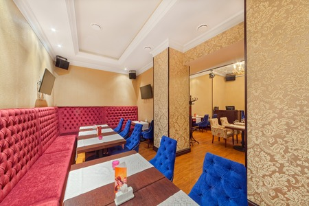 MOSCOW - SEPTEMBER 2014: The interior of the cafe grill bar NA MEDOVOY. Large burgundy corner sofa with high back in the room with tables and blue chairs 報道画像