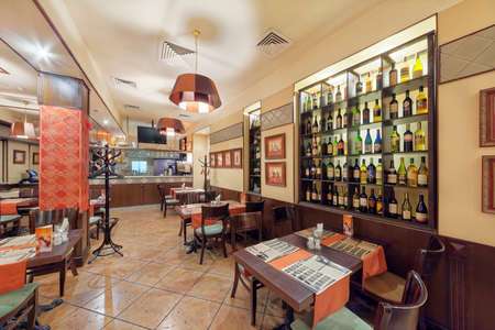 MOSCOW - SEPTEMBER 2014: The interior of the cafe grill bar NA MEDOVOY. Large hall with tables for visitors. Decorative wall shelf with wine bottles Editöryel