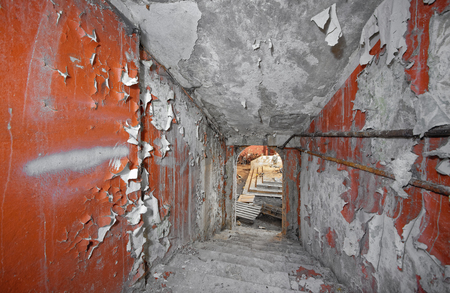 Descending down the concrete staircase in an abandoned bomb shelter with a fading paint and scuffed red walls