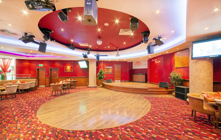 MOSCOW - SEPTEMBER 2014: Interior in modern style of the bar-restaurant FUSION PLAZA of Indian and European cuisine in red and beige color. The scene and the dance floor in the restaurant hall