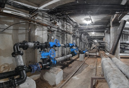 Blue valves on the water pipelines in an underground utility tunnel, heat pipeline and cable vault