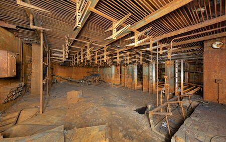 Rusty iron room with hooks for electrical cables in an abandoned scientific industrial laboratory Zdjęcie Seryjne