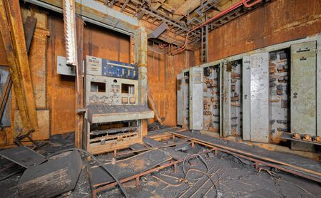 Old broken and covered with soot and rust control panel for power supply and cabinets for electrical equipment in abandoned after the fire industrial laboratory