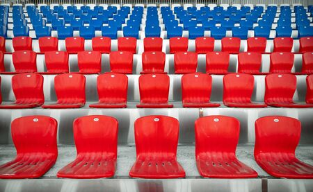Empty red and blue rows of plastic seats in the stands of the stadium Zdjęcie Seryjne