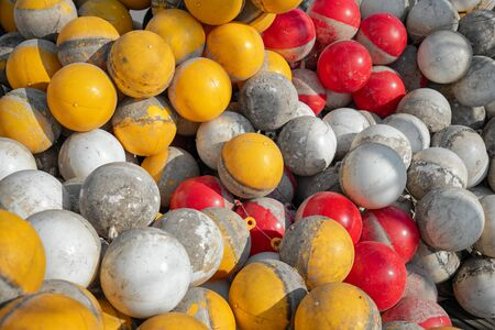 Many of plastic buoys, yellow, red and white color for sporting events covered in bloom after water