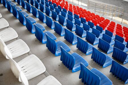 White, red and blue rows of plastic seats on the concrete bases of the sports building, stadium Zdjęcie Seryjne