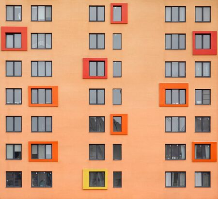 Many windows on the orange facade of the building. Architectural details in modern style Zdjęcie Seryjne - 136678470