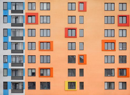 A lot of windows on the facade of a modern orange building with blue color. Architectural details. Zdjęcie Seryjne - 136678471