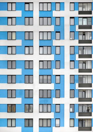 The facade of a blue modern high-rise building. Windows and balconies.