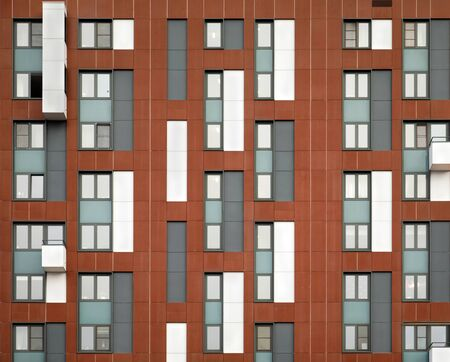 The facade of a brown modern high-rise building. Many different windows. Geometric architectural details