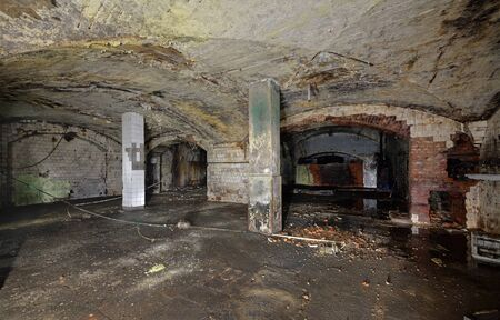 Interior of an abandoned underground wine cellar and warehouse of the 19th century. Peeling paint