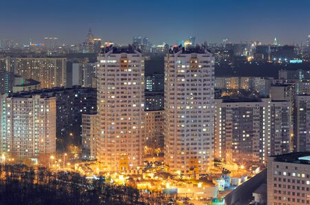 Two multi-apartment residential towers against the backdrop of the cityscape at night in a residential area Zdjęcie Seryjne