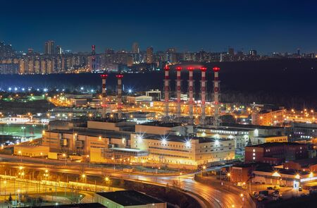 Night view from a height of a large city power station against the backdrop of the cityscape