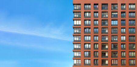 The modern brick facade of a high-rise building against the blue sky