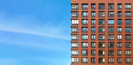 The modern brick facade of a high-rise building against the blue sky Zdjęcie Seryjne - 140671128
