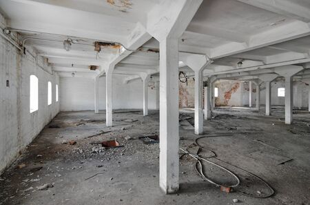 Empty industrial room of an old abandoned factory with white columns Zdjęcie Seryjne - 140671031