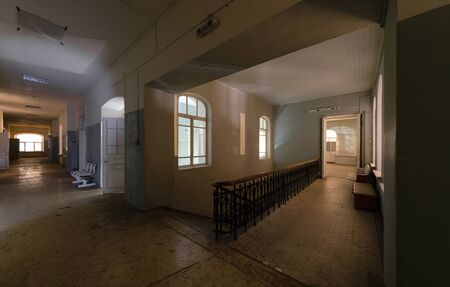 Ancient central staircase and corridor of an abandoned hospital, at night