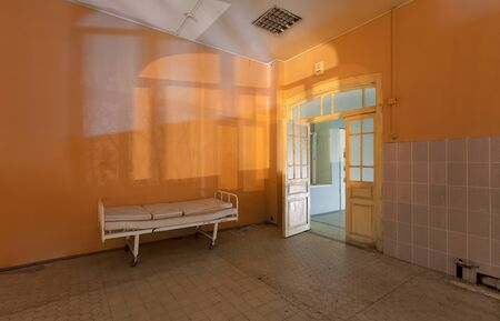 Silhouettes and shadows from the window on the wall of the room with a hospital bed in an abandoned hospital, at night