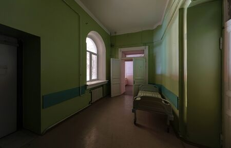 Green corridor with an empty hospital bed in an abandoned hospital Zdjęcie Seryjne