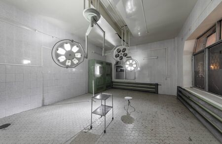 Operating theater with hanging shadowless light in an abandoned hospital. Zdjęcie Seryjne