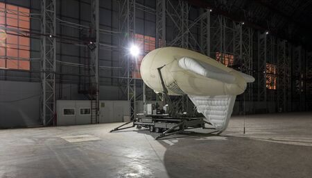 Small airship on a mooring platform in a giant aircraft hangar