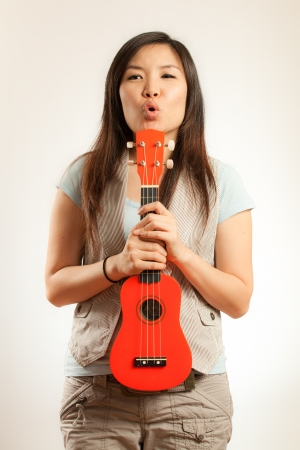 four person only: Asian woman enjoy her ukulele