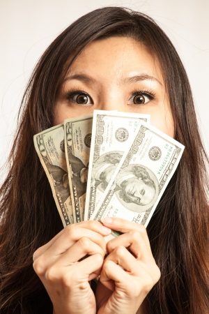 Happy asian woman holding dollar photo
