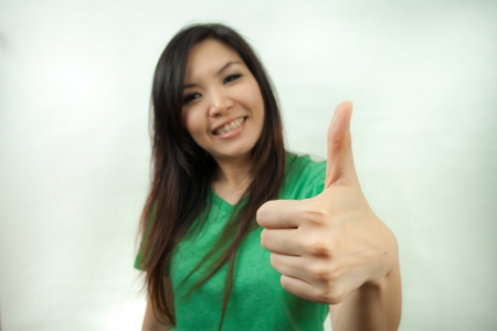 Asian woman in green set, thumb up photo