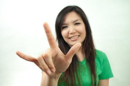te quiero: Mujer asiática en el conjunto verde, muestra de la mano Te quiero