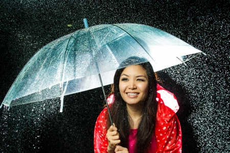Asian women under the rain with rain coat and umbrella photo