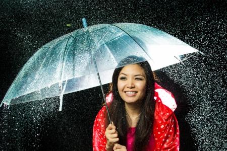 lluvia paraguas: Las mujeres asi?ticas bajo la lluvia con chubasquero y el paraguas