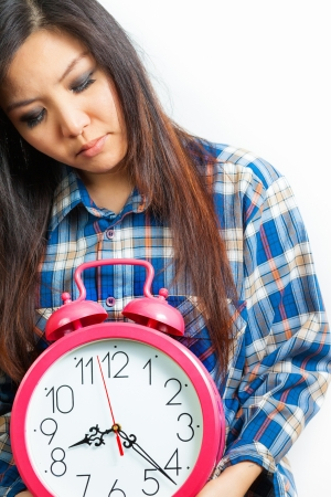 inconvenience: Asian woman holding an alarm clock in the  morning