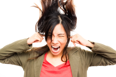 young asian woman annoyed by loud sound Stock Photo