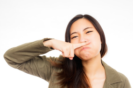 young asian woman annoyed by a bad smell photo