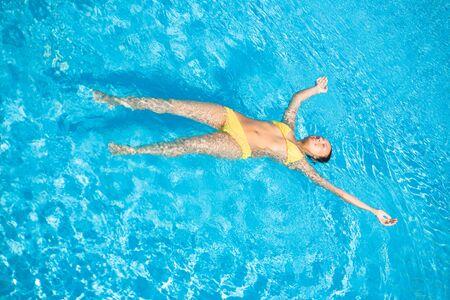skin diving: Young beautiful caucasian woman in bikini swimming in pool