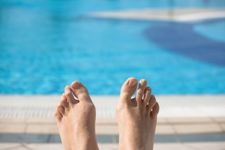 Feet of young caucasian woman laying by swimming pool photo