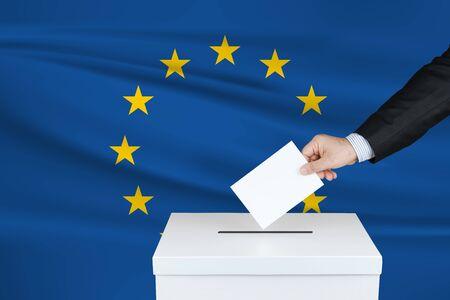 Election in European Union. The ballot box. Waved European Union flag on background.