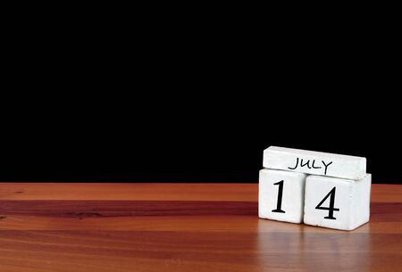 14 July calendar month. 14 days of the month. Reflected calendar on wooden floor with black background