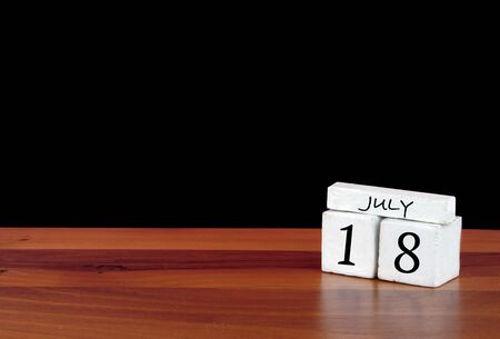18 July calendar month. 18 days of the month. Reflected calendar on wooden floor with black background 写真素材 - 150552720