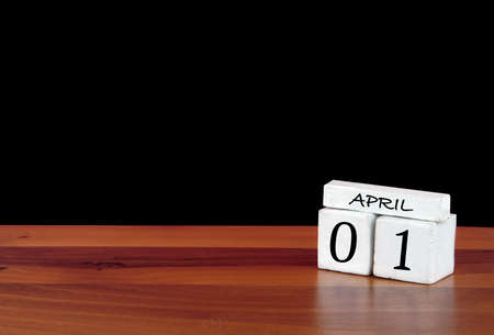1 April calendar month. 1 days of the month. Reflected calendar on wooden floor with black background