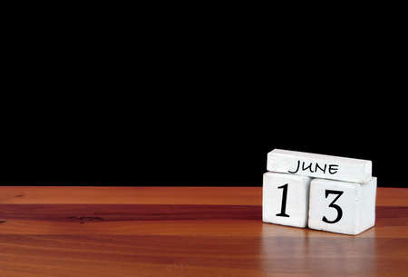 13 June calendar month. 13 days of the month. Reflected calendar on wooden floor with black background