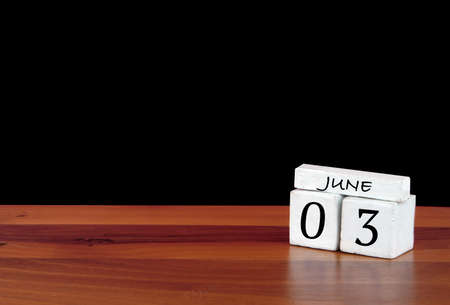 3 June calendar month. 3 days of the month. Reflected calendar on wooden floor with black background.