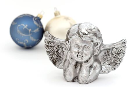 Silver christmas angel with christmas baubles in the background