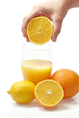 Half of an orange in a hand over a glass of orange juice on white background Standard-Bild
