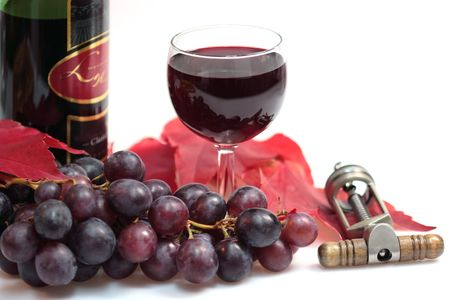 Red wine in a glass with grapes, vineleaves, wine bottle and cork skrew on white background Stock Photo